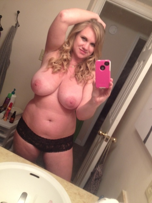 Chubby blonde takes a topless self shot of her boobs